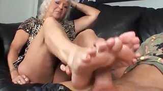 Blonde granny jerks off a stiff cock with her feet